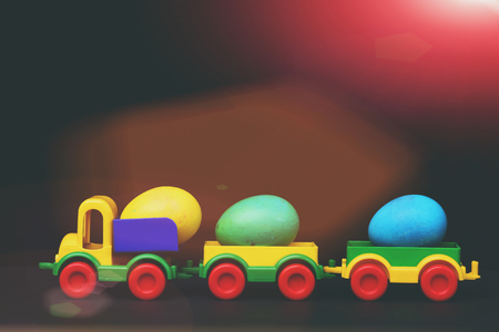hapyy easter holidays eggs and bunny set of traditional colorful eggs in plastic car toy or locomotive isolated on black background. Stock Photo