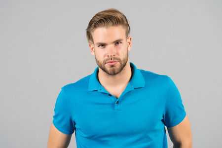 Macho in blue tshirt, fashion. Man with bearded face, blond hair, haircut. Barber salon, barbershop. Grooming, beauty, hair care. Fashion, style, trend.