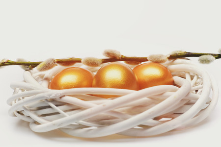 easter eggs set of traditional eggs painted in golden color inside woven wooden wreath with pussy willow branch isolated on white background. Happy Easter concept, luxury and success Stock Photo - 103253040