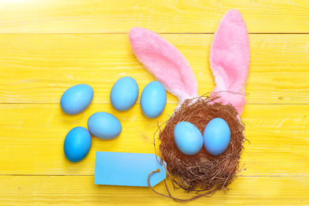 easter eggs set of traditional eggs painted in blue color with nest, tag and pink rabbit ears on yellow vintage wooden background. Happy Easter concept, copy space