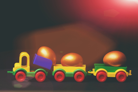 easter eggs set of traditional golden eggs in plastic colorful car toy or locomotive isolated on black background. Happy Easter concept, copy space