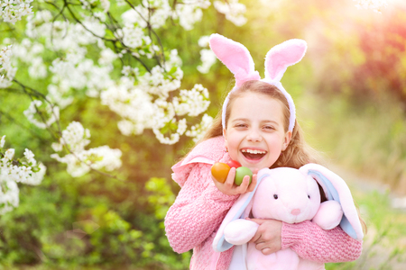 easter eggs Fertility and rebirth concept. Easter and spring celebration. Childhood, youth and growth. Happy girl holding pink rabbit toy and eggs. Child smiling with bunny ears in garden Stock Photo - 101923080