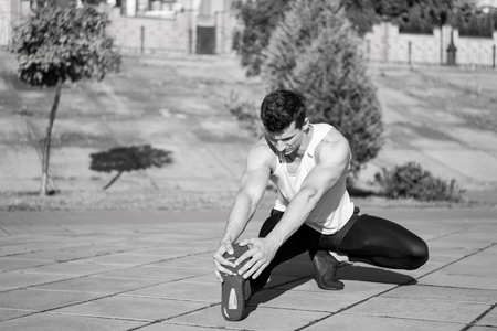 Fit macho in track suit on urban landscape. Athlete training on sunny summer day outdoors. Man stretching and warming up muscles before workout. Sport and fitness. Healthy lifestyle concept.