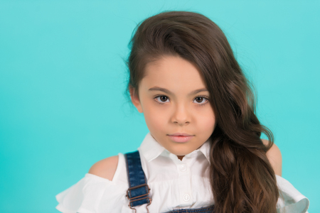 Beautiful little girl of primary school age with long flowing hair pose in front of the camera on blue background. 版權商用圖片