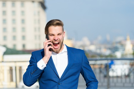 Happy manager talk on smartphone. Man with mobile phone on sunny terrace. Businessman in blue suit outdoor. Business communication, new technology and sms. Modern life and business lifestyle.