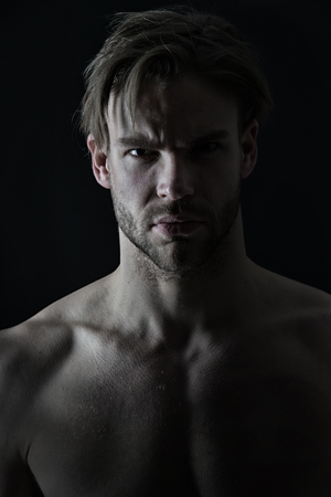 Sexy macho with bare chest muscles, sport. Man with bearded face skin and stylish hair, beauty. Mens beauty, skincare. Sport, fitness, bodybuilding concept. Bodycare or wellness and health