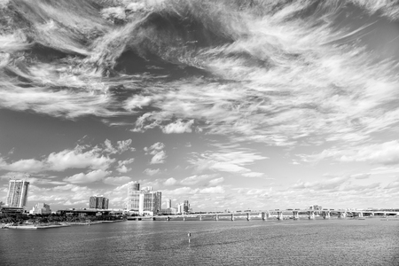 landscape view on water channel, bridge with transportation on road and urban houses on cloudy blue sky background sunny day outdoor in Miami. travelling and destinations