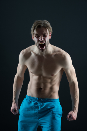 Bearded man shout with anger, health. Angry macho with fit bare torso, chest and belly, fitness. Athlete guy with six pack, ab, triceps and biceps muscles. Mens health and bodycare or wellness