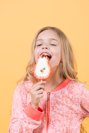 Little girl licks candy on stick. Concept of happy childhood, proper nutrition. Stok Fotoğraf