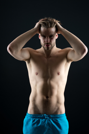 Strong athletic man fitness model torso showing six pack abs on black background