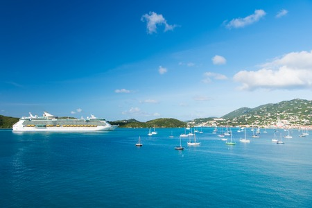 St.Thomas, British virgin island - January 13, 2016: cruise ship and yachts at seaside. Ocean liner in blue sea on sunny sky. Water transport and vessel. Travel by sea, wanderlust. Vacation on island.
