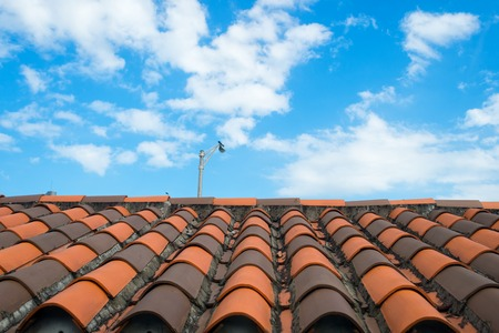 Roof with terracotta tile in miami, usa. Tile roofing on cloudy blue sky. Architecture and design. Rooftop with ceramic cover of classic clay material. Protection and shelter concept. Stock Photo
