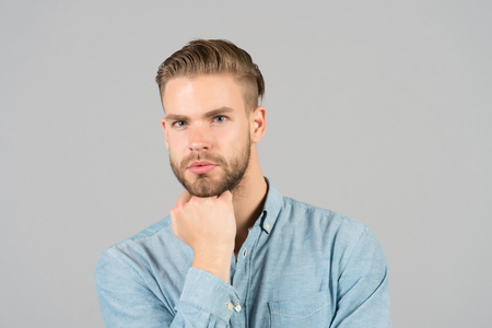 Guy with stylish hair touch beard with hand. Bearded man with healthy young skin. Macho with unshaven face and mustache. Beard grooming and hair care in barbershop. Skincare and mens beauty concept. Stock Photo