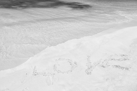 Love word written on white sand in st johns, antigua. Sea or ocean beach with turquoise water waves on sunny day. Summer vacation, holiday celebration on caribbean. Valentines day concept Stock Photo