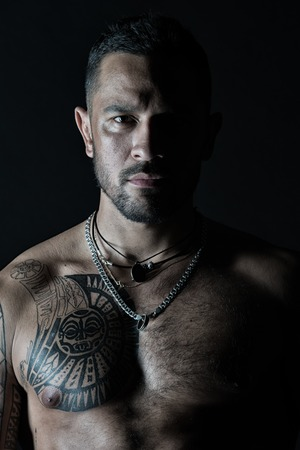Bearded man with tattooed chest. Macho with sexy bare torso. Fit model with tattoo art on skin. Sportsman or athlete with stylish beard and hair. Sport and fitness. Confidence and masculinity. Foto de archivo
