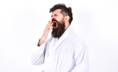Young man yawning with his mouth wide open. Hipster in white bathrobe isolated on white background. Tired macho in the morning after the party