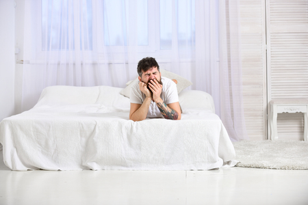Man in shirt yawning while lay on bed, white curtain on background. Macho with beard and mustache yawning, relaxing, having nap, rest. Tired and sleepy concept. Guy on sleepy tired face yawning