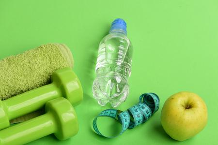 Dumbbells in bright green color, water bottle, measure tape, towel