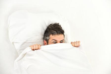 Nightmare concept. Guy hides face under blanket.