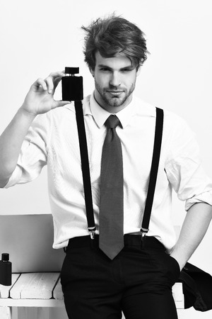 Caucasian stylish man posing with perfume