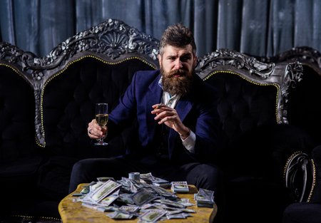 Millionaire in elegant suit smokes and drinks. Stock Photo