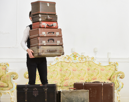Butler and service concept. Macho, elegant porter carries heavy pile of vintage suitcases. Man with beard and mustache wearing classic suit delivers luggage, luxury white interior background