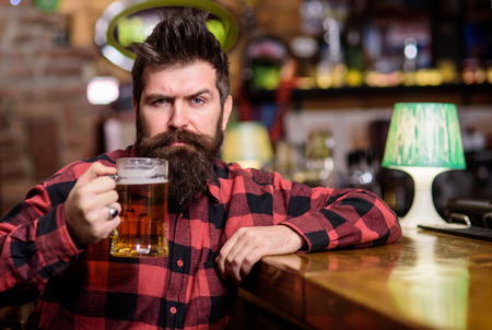 Hipster with beard holds glass with beer, raising up, cheers. Cheers concept. Guy spend leisure in bar, defocused background. Man on calm or serious face sit in bar or pub near bar counter Stock Photo