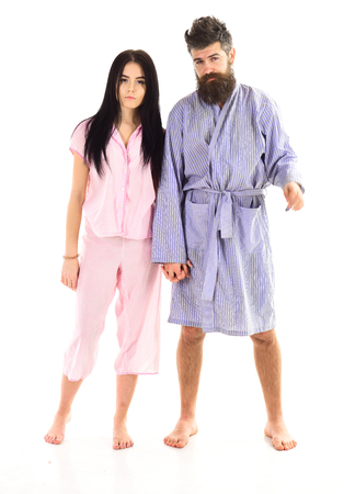 Couple, family on sleepy faces in clothes for sleep looks sleepy in morning. Couple in love in pajama, bathrobe. Insomnia concept. Couple hold hands together, isolated on white background