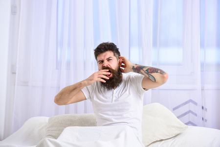 Man in shirt yawning while sit on bed, white curtain on background. Guy on sleepy tired face yawning. Sleepyhead concept. Macho with beard and mustache yawning, relaxing, having nap, rest