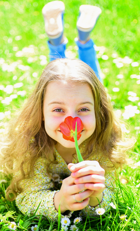 Girl lying on grass, grassplot on background. Child enjoy spring sunny day while lying at meadow with flowers. Girl on smiling face holds red tulip flower, enjoy aroma. Tulip fragrance concept Фото со стока