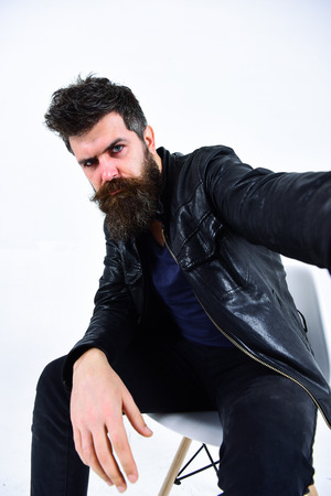 Man with beard and mustache on strict face looks at camera. Macho wears leather jacket, white background. Menswear and fashion concept. Hipster looks serious while sitting on chair in stylish outfit