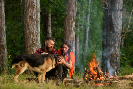 Couple play with german shepherd dog near bonfire,