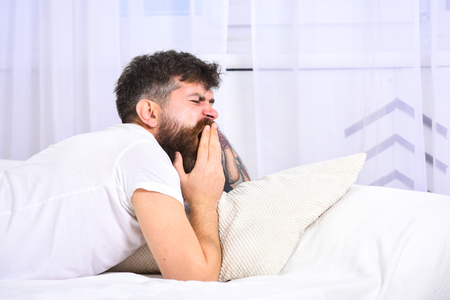 Man in shirt yawning while laying on bed, white wall and curtain on background. Guy on sleepy tired face yawning. Macho with beard and mustache yawning, relaxing, having nap, rest. Sleepyhead concept
