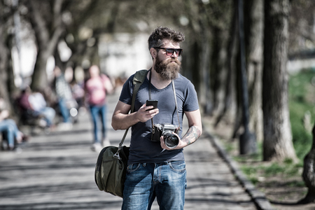 Bearded man carries bag on shoulder and holds camera. Photographer concept. Man with long stylish beard using smartphone while walking. Man with beard on confident face, urban background, defocused