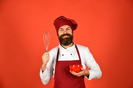 Chef with red plate and whipping utensil. Kitchen tools concept.