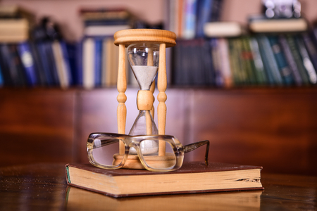 Librarian attributes concept. Hourglass counting time near old fashioned eyeglasses. Sand falling down inside of hourglass. Hourglass, old book and eyeglasses on wooden table, library on background