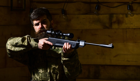 Man with beard wears camouflage clothing, wooden interior background. Hunter, brutal hipster with gun aiming before hunting, copy space. Huntsman concept. Macho on strict face at gamekeepers house Stock fotó