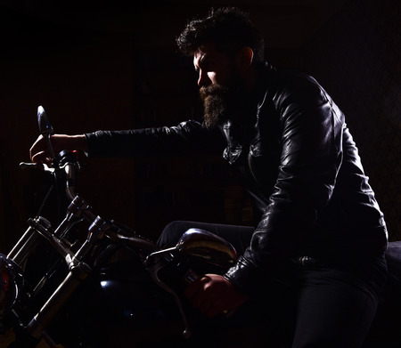 Macho, brutal biker in leather jacket riding motorcycle at night time, copy space. Man with beard, biker in leather jacket sitting on motor bike in darkness, black background. Night racer concept