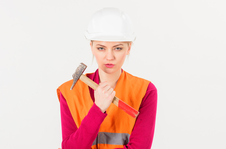 young woman with hard hat and hammer getting ready Stock Photo