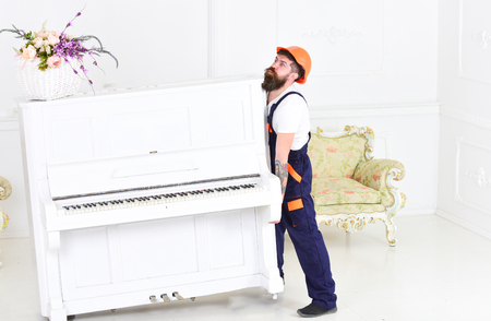 Guy from transportation company moving old piano alone. Tired guy lifting heavy stuff Stock Photo