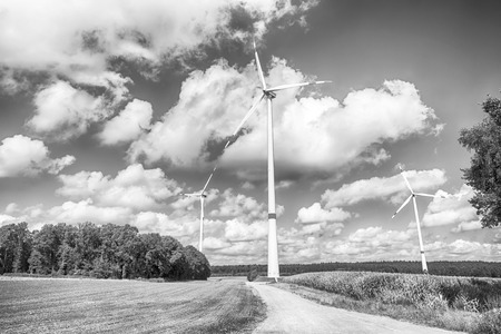 Alternative energy source. Turbines on field on cloudy blue sky. Wind farm in Lower Saxony, Germany. Global warming, climate change. Eco power, green technology concept.