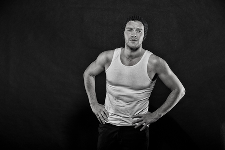 Man with muscular arms hold hands on hips. Masculinity concept. Macho on confident face with strong muscles look brutal, black background. Man in hat and sleeveless undershirt looks slovenly.
