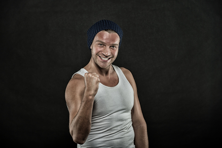 Macho on smiling face with strong muscles look brutal, black background. Man with muscular arms squeezing fist tight, as gesture. Masculinity concept. Man in hat and sloven sleeveless undershirt.