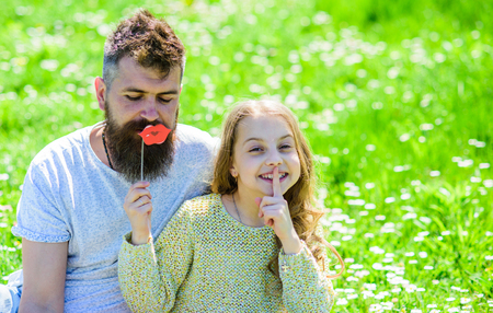 Family spend leisure outdoors. Dad and daughter sits on grass at grassplot, green background. Child and father posing with lips photo booth attribute while kid shows silence gesture. Secret concept Stock Photo