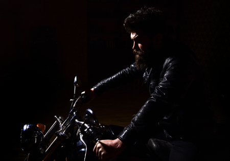 Masculinity concept. Man with beard, biker in leather jacket sitting on motor bike in darkness, black background. Macho, brutal biker in leather jacket riding motorcycle at night time, copy space Stock Photo