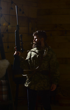 Hunter concept. Man with beard wears camouflage clothing, dark background. Macho on strict face at gamekeepers house ready for hunting. Hunter brutal with gun and horns of deer, lighted in darkness