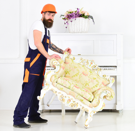 Relocating concept. Courier delivers furniture in case of move out, relocation. Man with beard, worker in overalls and helmet lifts up armchair, white background. Loader moves armchair for move out Reklamní fotografie