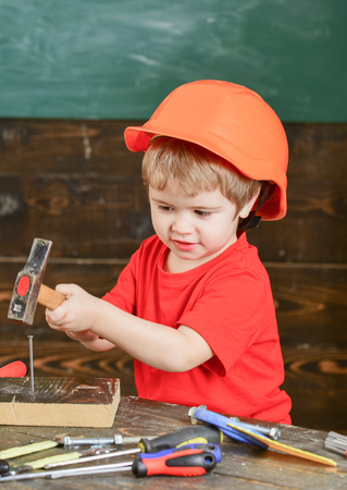 Safety at workplace. Little kid in orange helmet hammering nails. Cute boy playing with tools Stock Photo