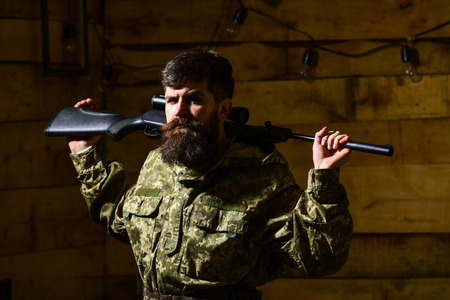 Hunter, brutal hipster on strict face with gun ready for hunting. Man, gamekeeper with beard wears camouflage clothing, carries rifle on shoulders, wooden interior background. Masculinity concept