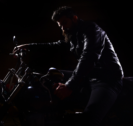 Macho, brutal biker in leather jacket riding motorcycle at night time, copy space. Night racer concept. Man with beard, biker in leather jacket sitting on motor bike in darkness, black background